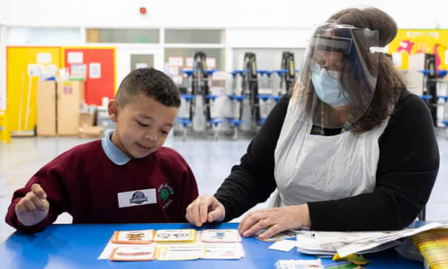 A child has a reading lesson with a teaching assistant wearing a face mask and visor at Glan-Yr-Afon primary school in Cardiff, Wales.