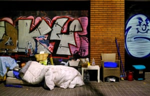 Barcelona, Spain. A woman sleeps on an empty street, during a night-time curfew set as part of a state of emergency in an effort to control the outbreak of coronavirus