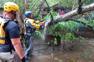 Search and rescue crew members clear a fallen tree in Fajardo.