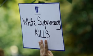 A woman holds a sign during a rally against guns and white supremacy in the wake of mass shootings in Dayton and El Paso in front of the White House, 6 August 2019.