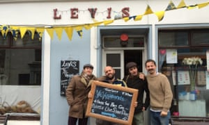 Musicians stands with a blackboard advertising their gig at Levis Corner House Ballydehob, in West Cork, Ireland.
