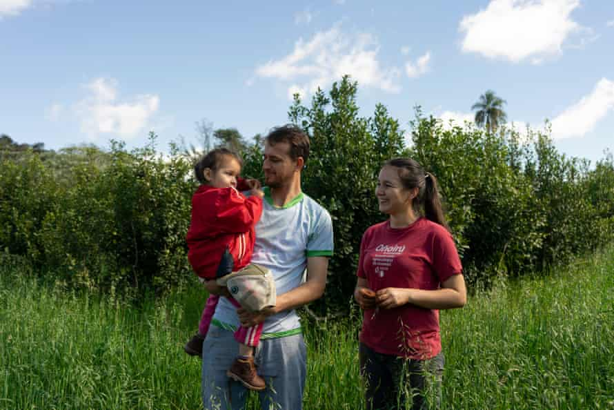 Pedro Vega and Celia Motta, members of Onoiru, walk with their young daughter Pilar through their agroecological crop of yerba mate in the fields of Edelira, in the department of Itapua.