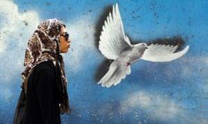 A woman walks past a dove mural in Tehran.