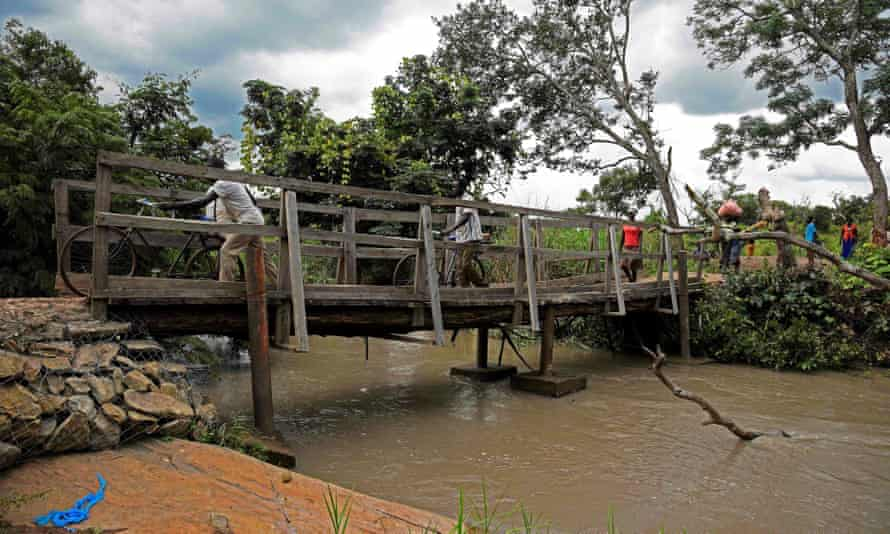Refugees from South Sudan cross a bridge over the Kaya river in Koboko district in 2017