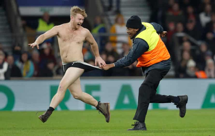 A streaker is grabbed by a steward as he runs on the pitch during the England v Australia autumn international rugby union match at Twickenham Stadium on November 24th 2018