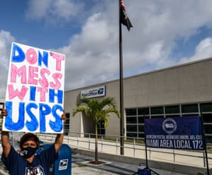 People attend a rally in support of the US Postal Service (USPS) in Miami, Florida. Americans are expected to vote by mail in massive numbers due to the coronavirus pandemic, but the US president Donald Trump has opposed more funding for the cash-strapped USPS, acknowledging the money would be used to help process ballots.