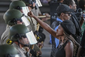 Ebonay Lee holds up her fist at a line of sheriff's deputies during a protest against the killing of a black man in El Cajon, California