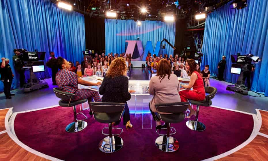 The backs of Brenda Edwards, Nadia Sawalha, Coleen Nolan and Andrea McLean, sitting before a live Loose Women audience, the studio lights in the ceiling