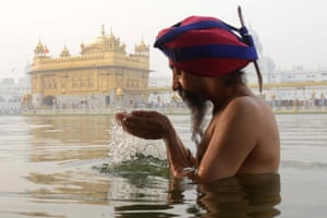 Indian Sikh devotee bathes in water
