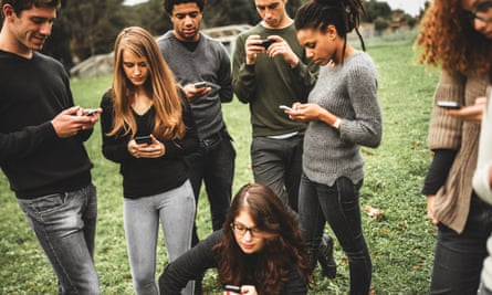 Group of  diverse young people tapping away at phones