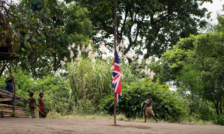 Children of Yaohnanen village play as the Union Jack flies at half mast