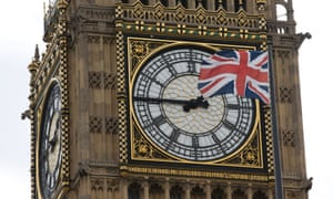 A Union flag flapping in the wind in front of Big Ben.