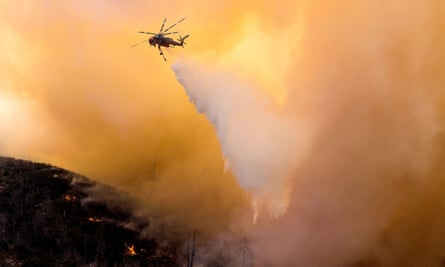 A helicopter makes a water drop over the Bobcat fire in the Angeles national forest in Los Angeles, California, 17 September 2020.