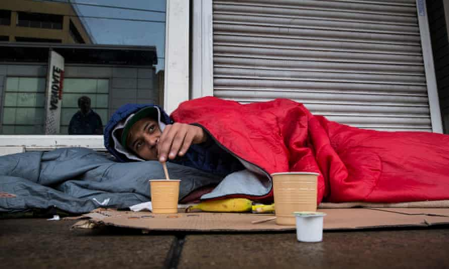 A young man waking up to a drink and snack left by volunteers after he spent the night sleeping alone on the streets near Piccadilly in Manchester.