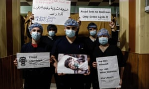 Medical staff in Damascus hold placards condemning a suspected chemical weapons attack on the Syrian town of Khan Sheikhun
