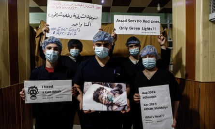 Medical staff at Damascus Countryside Specialised Hospital hold placards condemning a suspected chemical weapons attack on the Syrian town of Khan Sheikhun.