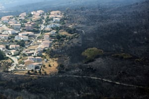 An aerial view shows houses adjacent to terrain scorched by wildfire near the village of Biguglia, Corsica