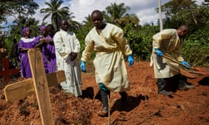 Health workers take part in the funeral of a woman infected with Ebola in her home village of Mutwanga, in North Kivu province, Democratic Republic of the Congo.