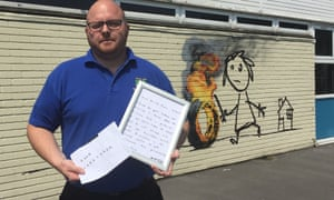 Site manager Jason Brady holding a letter left by Banksy at Bridge Farm primary in Bristol