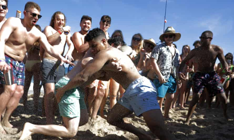 Two men wrestle each other as spring break revelers look on on March 17 in Pompano Beach, Florida. As a response to the coronavirus pandemic, the governor ordered all bars be shut down for 30 days.