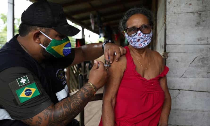 A health worker administers a Covid-19 vaccine in Brazil.