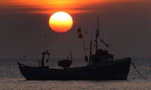A fishing boat against the backdrop of a colourful orange sunset