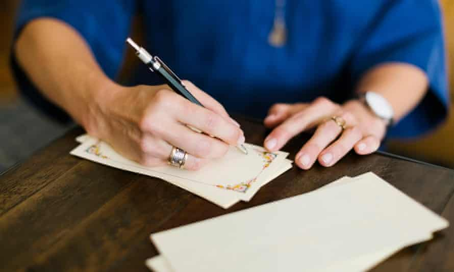 Close-up of woman writing letter.