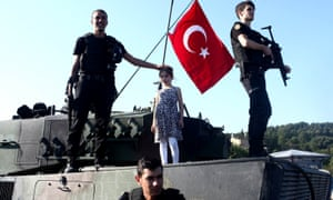 Police officers loyal to the government stand atop tanks abandoned by Turkish army soldiers