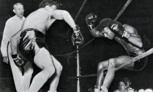 Sugar Ray Robinson falls through the ropes of a Detroit ring under the impact of Jake LaMotta's fists in 1943.