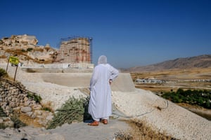 An elderly woman looks at the newly built stone wall near the 12,000-year-old city of Hasankeyf