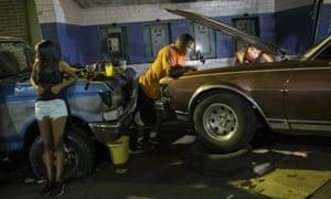 Men spend the evening repairing a car outside their home in Caracas, Venezuela.