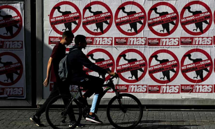 """Pedestrians pass posters that read """"No to the payment of the debt. Break with the IMF"""", in Buenos Aires."""