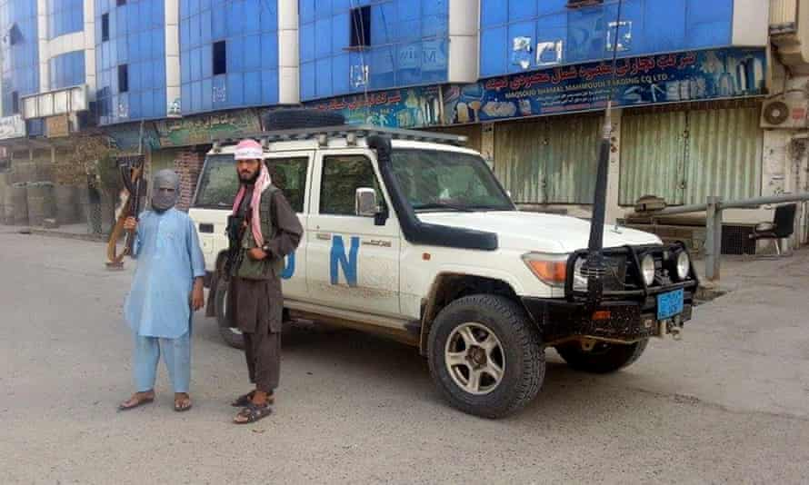 Taliban fighters in Kunduz pose next to a UN vehicle which they have taken.
