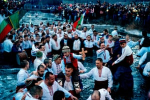 Kalofer, Bulgaria. Men and boys perform the traditional 'Horo' dance in the icy waters of the Tundzha River, as part of Epiphany celebrations