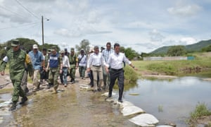 President Enrique Peña Nieto, right, inspects affected areas in Pueblo state. He was booed by students in his home state of Mexico.