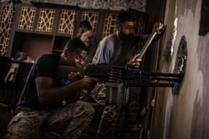 A fighter for the Libyan forces affiliated to the Tripoli government searches for sniper positions on the frontline in Sirte