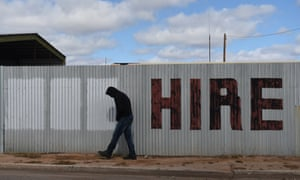 A man walks past a hand painted hire sign