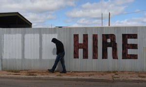A man walks past a hand painted hire sign in the NSW outback town of Bourke