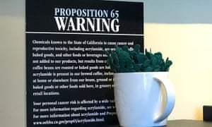 Proposition 65 warning sign posted behind a coffee mug at a Starbucks coffee shop in Burbank, California. A judge issued a final ruling on Monday requiring coffee to carry cancer warning labels in California.