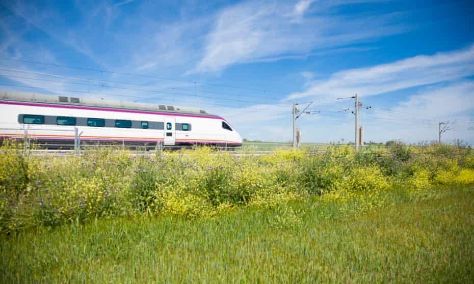 A high-speed train flies through the Spanish countryside