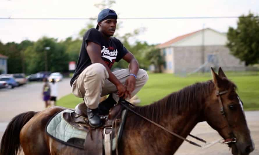 A young man crouched on a horse in the documentary Hale County This Morning, This Evening.