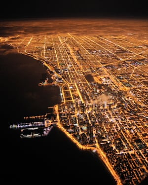 Lights of Chicago burn brightly at night under a blanket of clouds.