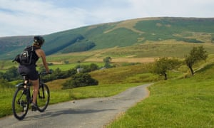 A cyclist rides past Fair Oak Fell in the Forest of Bowland.