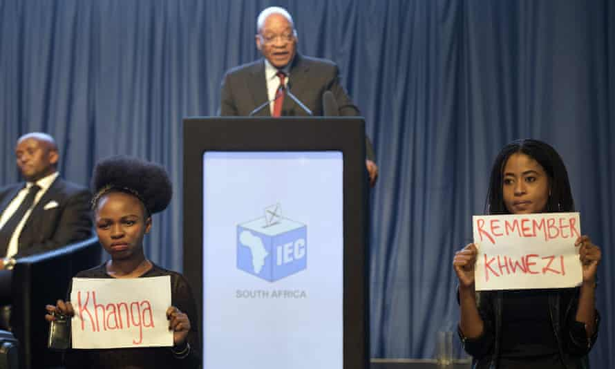 Protesters hold up placards during Jacob Zuma's speech at the announcement of the results of South Africa's municipal elections in Pretoria.