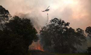 A water bomber drops its load on a bushfire