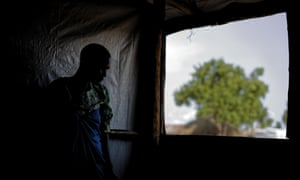 A South Sudanese refugee who was raped for several days by soldiers stands by a window at a women's centre run by the International Rescue Committee, in Bidi Bidi, Uganda