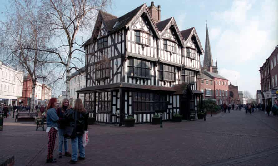 Group of young women next to a timber framed house in Hereford town centre