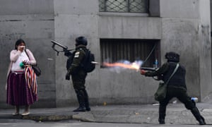 """BOLIVIA-CRISIS-MORALES-RESIGNATION-MARCH-AFP PICTURES OF THE YEA<br>- AFP PICTURES OF THE YEAR 2019 - Riot police fire tear gas to disperse supporters of Bolivian ex-President Evo Morales and locals discontented with the political situation during a protest in La Paz on November 13, 2019. - Bolivia's exiled ex-president Evo Morales said Wednesday he was ready to return to """"pacify"""" his country amid weeks of unrest that led to his resignation. (Photo by RONALDO SCHEMIDT / AFP) (Photo by RONALDO SCHEMIDT/AFP via Getty Images)"""