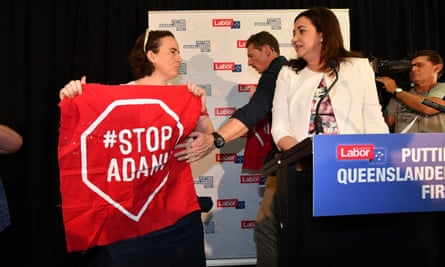 Anti-Adani coalmine protestors invade the stage as Queensland premier Annastacia Palaszczuk (right) delivers a speech.