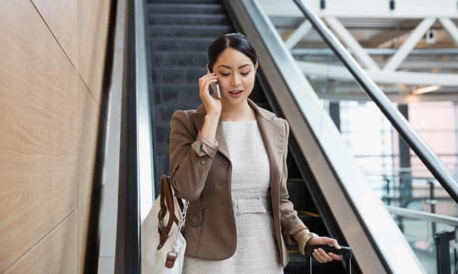 Businesswoman with mobile phone on escalator at airport